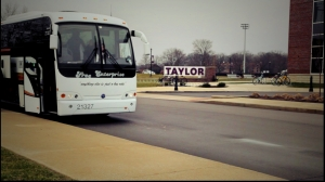 The bus waits in front of the Taylor sign at the Campus Center.