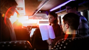 Choir members sing together on the bus.