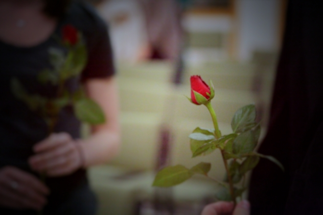 A performer holds a rose.