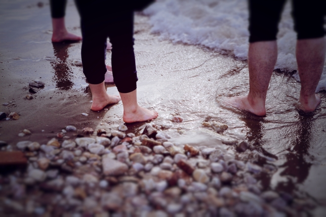 People dip their feet in the Aegean sea.