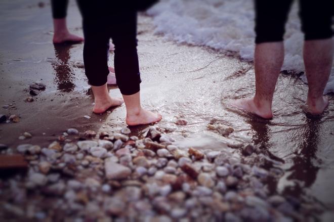 People dip their feet in the Aegean sea.