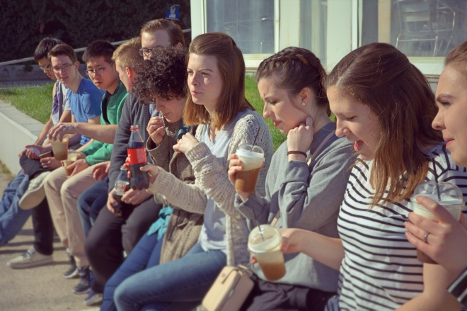 Taylor students sit along a wall drinking coffee.