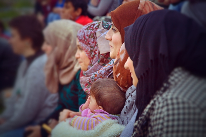 A Syrian woman holding her baby watches Taylor Playback Theatre.