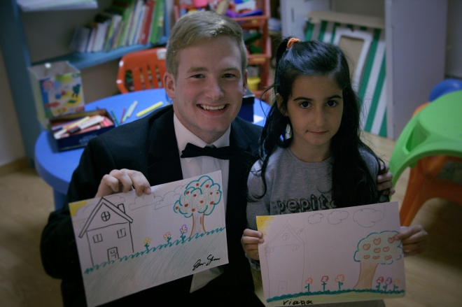 A Sounds member poses with a refugee child and their drawings.