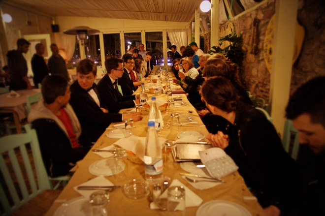 Taylor students and their guests from the Syrian camp eat dinner together around a long table.