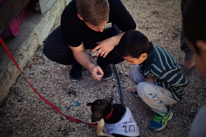 Sounds member Evan Shaw plays with a refugee family's puppy named Jimmy.